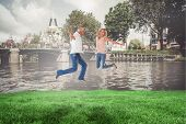 Excited couple cheering and jumping against sunny day by the river