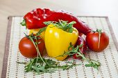 Red juicy tomatoes, leaves of arugula and sweet pepper