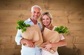 Happy couple carrying paper grocery bags against bleached wooden planks background