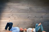 Mature couple lying and smiling against bleached wooden planks background