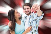 Happy young couple showing new house key against digitally generated twinkling light design