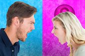 Angry couple shouting during argument against pink and blue