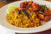 stock photo of crispy rice  - Crispy spicy Kadai Paneer Tofu with tamarind rice and lime wedges - JPG