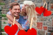 Man giving his pretty girlfriend a piggy back against hearts hanging on a line
