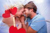 Cute couple relaxing on bed smiling at each other against hearts hanging on a line