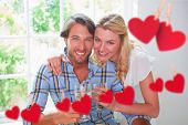 Cute smiling couple enjoying white wine together against hearts hanging on a line