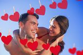 stock photo of tan lines  - Handsome man carrying his girlfriend on his back against hearts hanging on a line - JPG