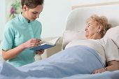 Caregiver Reading Ill Patient Book