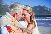 image of couple sitting beach  - Smiling couple sitting on the beach under blanket against hearts hanging on the line - JPG