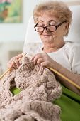 Grandma Lying In Bed And Knitting