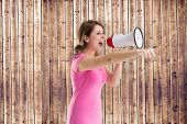 Angry woman with megaphone against wooden planks