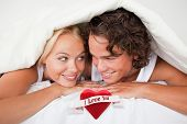 Couple under a duvet with a knowing smile against heart with scroll