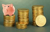 Piggy bank standing on stack of coins on gray background