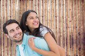 Happy casual man giving pretty girlfriend piggy back against wooden planks