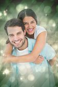 Happy casual man giving pretty girlfriend piggy back against light design shimmering on green
