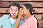 Brunette whispering secret to her boyfriend against wooden planks background