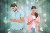 Happy couple sending text messages against light design shimmering on green