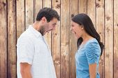 Angry couple shouting at each other against wooden planks