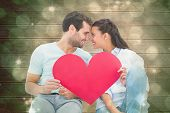 Cute couple sitting holding red heart against light design shimmering on green