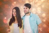 Happy casual couple smiling together against light design shimmering on red