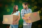 Happy young couple with moving boxes against close up of christmas lights