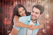 Happy casual man giving pretty girlfriend piggy back against light design shimmering on red