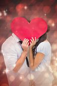 Couple covering their kiss with a heart against light design shimmering on red
