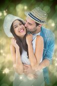 Happy hipster couple hugging and smiling against light design shimmering on green