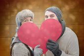 Attractive young couple in warm clothes holding red heart against black abstract light spot design