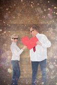 Older affectionate couple holding red heart shape against white snow and stars on black