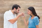 Angry couple pointing at each other against wooden surface with planks