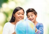family, children, education, geography and people concept - happy mother and daughter with globe over green background
