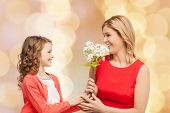 people, holidays, relations and family concept - happy little daughter giving flowers to her mother over beige lights background