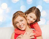 people, happiness, love, family and motherhood concept - happy mother and daughter hugging over blue lights background
