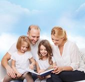 family, childhood, dream and people - smiling mother, father and little girls reading book over blue sky background