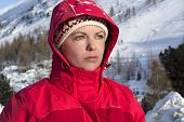 Woman With Red Jacket Looks Into The Distance In The Mountains