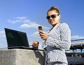 Woman With Mobile Telephone And Laptop