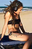 Girl with headphones on the beach