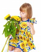 Beautiful little girl sees a beautiful yellow flower