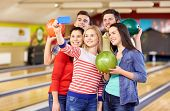 people, leisure, sport, friendship and entertainment concept - happy friends taking selfie with smartphone in bowling club