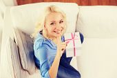 holiday, celebration, home and birthday concept - smiling young woman with gift box and making shh gesture at home