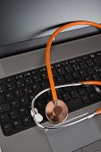 Laptop With Orange Stethoscope On The Grey Background