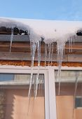 Icicles On Eaves House On Sunny Day