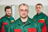 Group portrait of service repairman in uniform in automobile service station garage