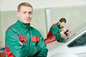 Automobile glazier repairman portrait in front of worker repairing car windscreen in auto service station garage