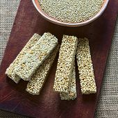 picture of quinoa  - Overhead shot of quinoa cereal bars one with honey the other mixed with amaranth with bowl of raw white quinoa on wooden board photographed with natural light  - JPG