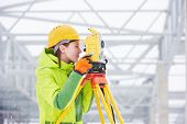 female surveyor worker working with theodolite transit equipment at road construction site outdoors