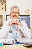 Smiling old physician sitting at his desk in the office