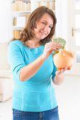 Woman putting money in piggybank, concept of saving