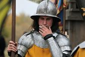 MILOVICE, CZECH REPUBLIC - OCTOBER 23, 2013: Actor dressed as a medieval guard smokes during the filming of the new movie The Knights directed by Carsten Gutschmidt near Milovice, Czech Republic.